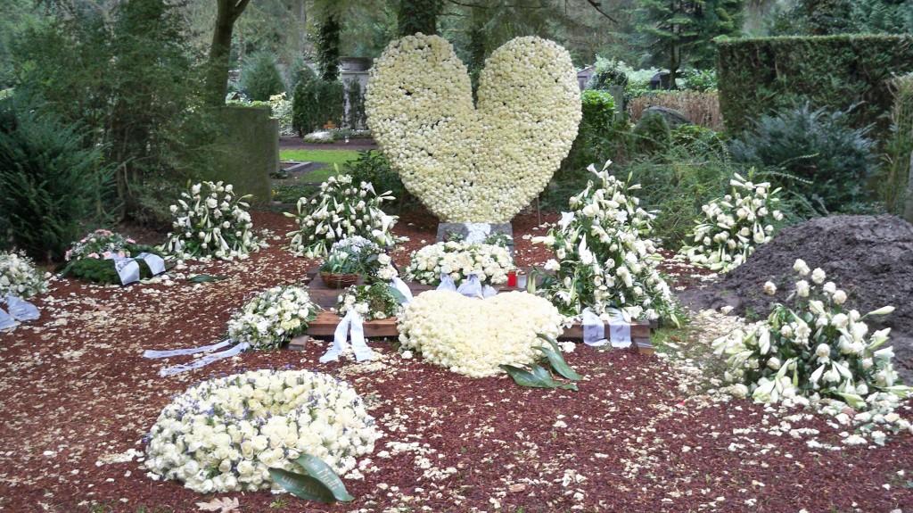 Herz aus Blumengesteck auf Grab