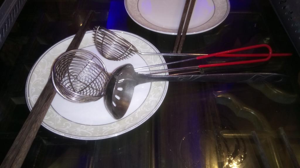 Suppenkelle und Sieb liegen auf einem Teller